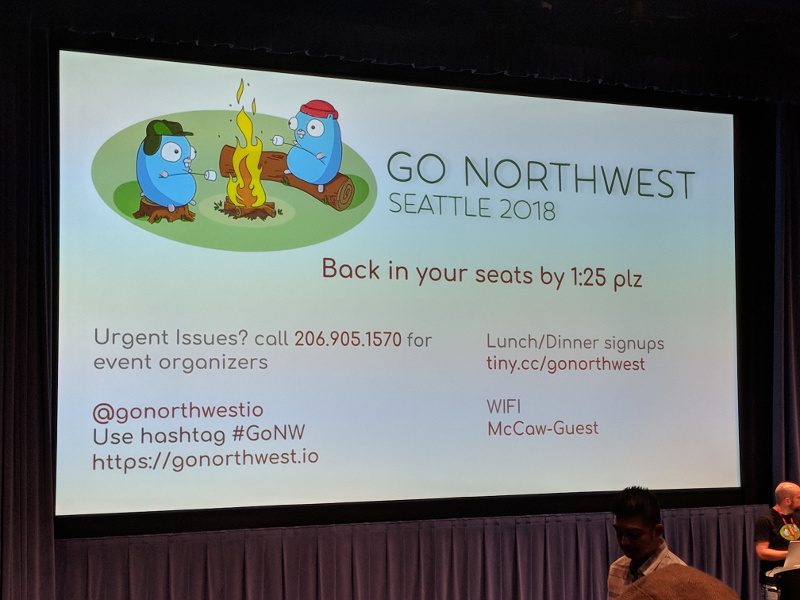 Projector screen showing a slide describing a break at the conference and displaying the Twitter handle @gornorthwestio, the hashtag #GoNW, the website https://gonorthwest.io, emergency contact information for the organizers, lunch/dinner sign ups, and the WiFi SSID