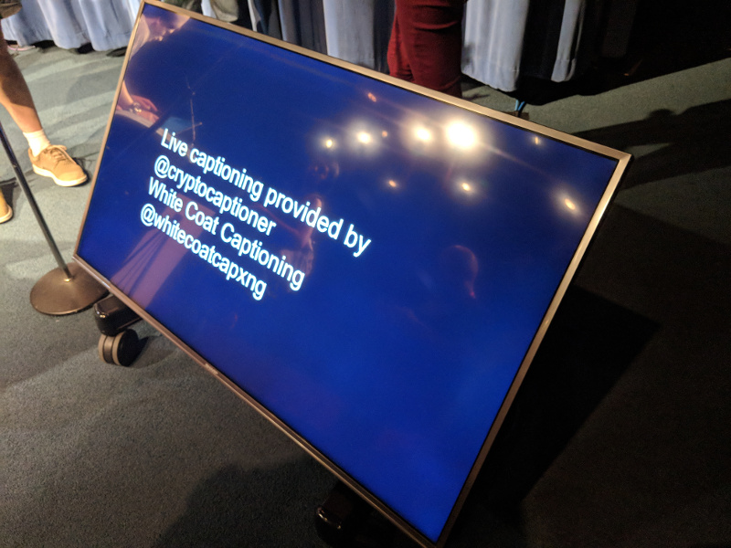 TV screen used to show live captions during the talks. Current text: Live captioning provided by @cryptocaptioner White Coat Captioning @whitecoatcapxng