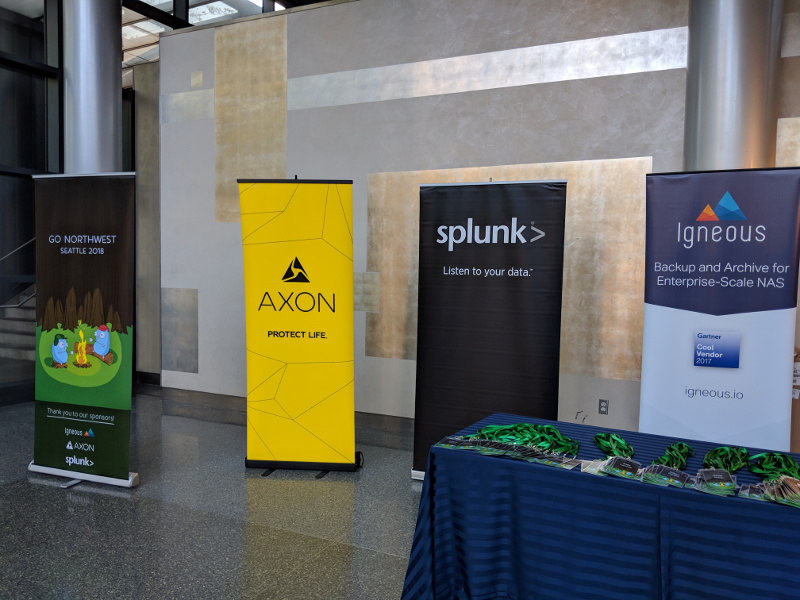 Signs at the registration table for Go Northwest.  From left to right: Go Northwest conference sign, Axon sponsor sign, Splunk sponsor sign, and Igneous sponsor sign.